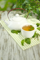 Teapot and cup of herbal tea with fresh mint on wooden table