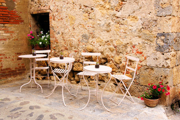 Fototapete - Cafe tables and chairs outside in a quaint corner of Tuscany