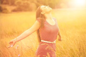 Summer Fun. Young happy woman enjoying sunlight on the wheat mea