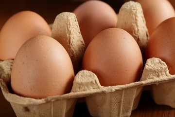 Close up of brown chicken eggs in carton box.