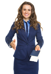 Smiling business woman giving passport with air tickets