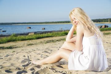Woman in white dress indulgence on beach