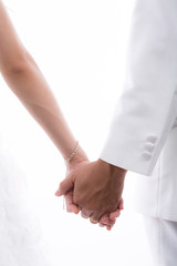 Closeup of  bride and groom holding hands isolated on white back