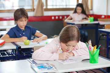 Schoolgirl Drawing While Leaning On Desk In Classroom