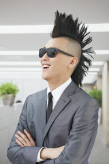 Well-dressed young man with Mohawk and sunglasses smiling