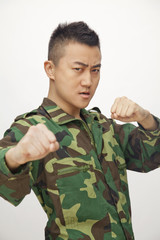Portrait of man in military uniform putting up fists to fight