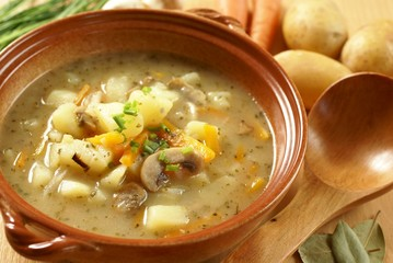 Bowl with potato soup, wooden ladle and food ingredients.
