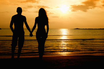 Couple enjoying their time at the sunrise on the beach