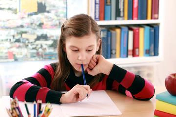 Mädchen macht Hausaufgaben am Schreibtisch