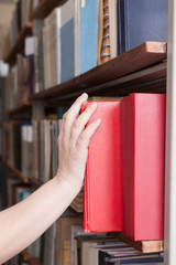 woman takes a book from the shelf