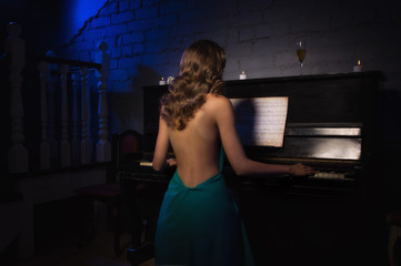 Beauty woman in evening dress playing piano