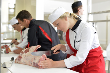 Girl cutting meat during butcher training course