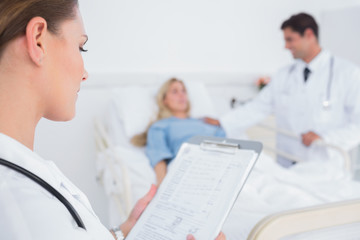 Doctor reading folder of a patient