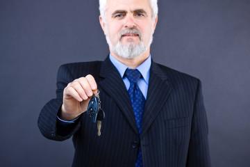 Studio shot of  business man with keys of car on the dark backgr