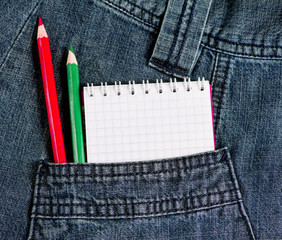 Notebook and pencils in jeans pocket