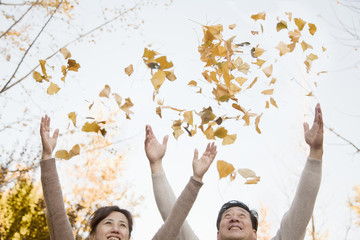 Mature Couple Throwing Leaves into the Air