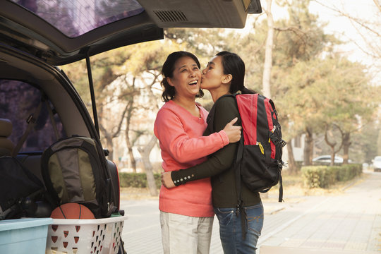 Mother and daughter embracing behind car on college campus