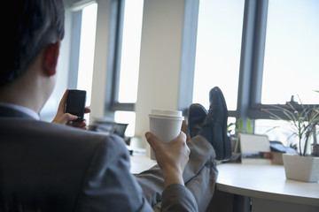 Businessman with feet up drinking coffee and text messaging