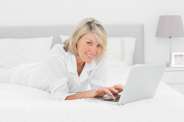 Smiling woman using her laptop on her bed looking at camera