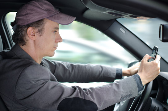 Man driving and texting someone on his cell phone