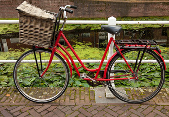 Red Bicycle with Basket Parked Beside Canal in Holland