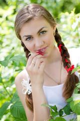 Young happy teen girl eating raspberry in garden