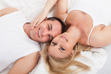 Happy Couple Lying On Bed