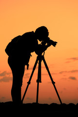 Photographer on work in sunset- Silhouette