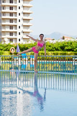 Young woman does morning exercises on poolside