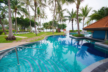 Swimming pool beside the sea with coconut tree.