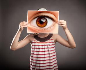 little girl holding an eye