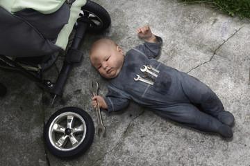 Fototapeta baby lying on the ground and repairing your stroller obraz
