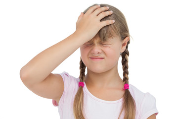 Little girl suffering from headache and touching her head