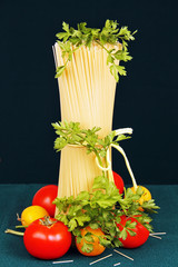 raw spaghetti tie a ribbon, tomatoes and parsley.