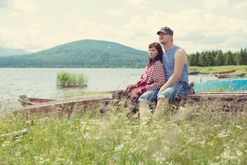Happy young couple relaxing on the shore of the mountain lake