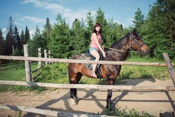 Young caucasian woman riding a brown horse, horizontal shot