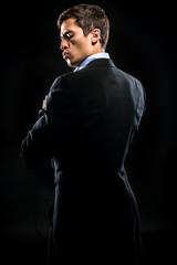Man in elegant black suit posing over black background