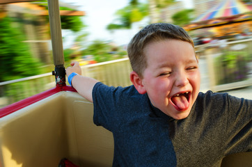 Happy child enjoying spinning ride at carnival with motion blur