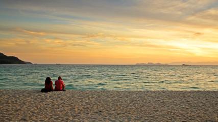 Couple sitting on beach to enjoy sunrise at Koh Lipe