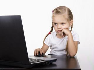 Девочка сидит за столом и спокойно работает за ноутбуком