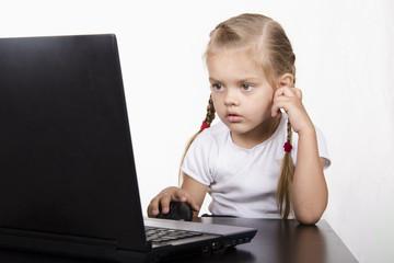 Девочка сидит за столом и работает за ноутбуком