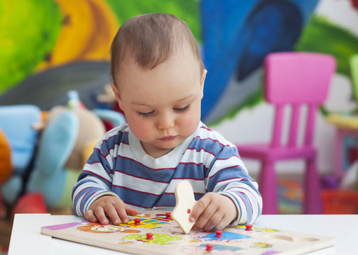 Toddler or a baby child playing with puzzle in a nursery.