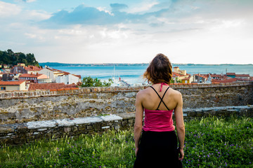 Young woman looking at the sea and her small village from a hill