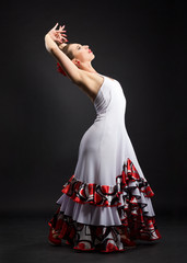 Spanish woman dancing flamenco on black