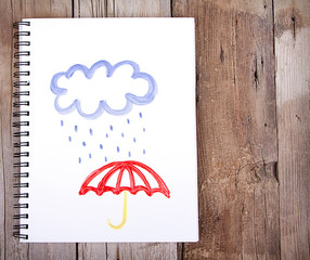 Painting of cloud and rain with umbrella on notebook