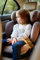 Adorable little girl sitting in car seat