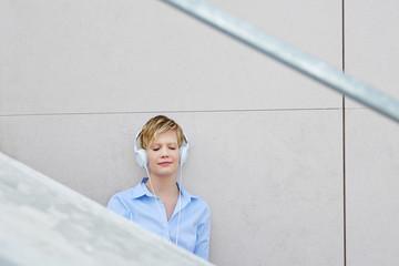 Junge Frau mit Kopfhörer in der Stadt