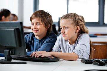 Boy And Girl Using Desktop Pc In School Computer Lab