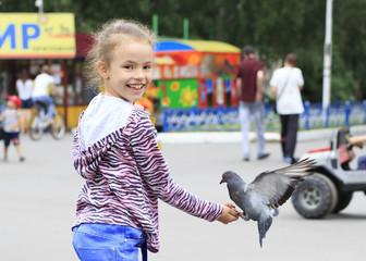 Joyful little girl with a dove on hand (feeding birds seeds)