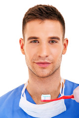 A young man brushing his teeth isolated on white background
